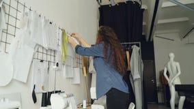Niskiego kąta widok patrzeje nakreślenia młody projektant mody i wiszący rysunki na ścianie w nowożytnym loft projektujemy studio zdjęcie wideo