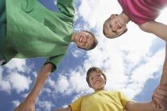 Niskiego kąta widok Trzy dzieciaka Trzyma ręki obrazy stock