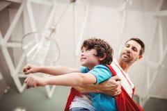 Niskiego kąta widok trzyma rozochoconego syna jest ubranym bohatera kostiumowy ojciec fotografia stock