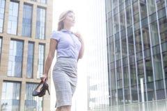 Niskiego kąta widok ufne bizneswomanu mienia szpilki podczas gdy stojący na zewnątrz budynków biurowych Obraz Stock