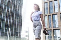Niskiego kąta widok ufne bizneswomanu mienia szpilki podczas gdy stojący na zewnątrz budynków biurowych Obrazy Royalty Free