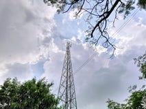 Niskiego kąta widok telekomunikacji wierza Przez Drzewnego baldachimu Przeciw Chmurnemu niebu obraz royalty free
