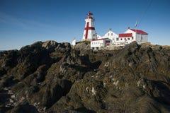 Niskiego przypływu pokazów Skalisty brzeg przy Kierowniczą schronienie latarnią morską w Kanada obraz stock