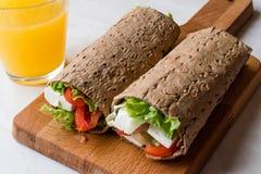 Niskokalorycznej diety opakunek z serem, pomidorami, sałatką i sokiem pomarańczowym, fotografia stock