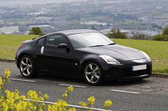 Nissan Sports Car on Hill Top. Beautiful view of city with black sports car Nissan 350z Royalty Free Stock Image