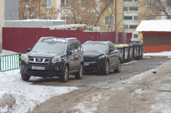 Nissan X-Trail and Infiniti FX. SARANSK, RUSSIA - JANUARY 1, 2017: Nissan X-Trail and Infiniti FX parked at city street. Photo taken at cloudy day Royalty Free Stock Photography