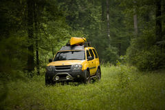 Nissan Xterra in woods. With a yellow kayak on top Stock Photos