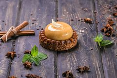 Nisse med karamell-, nougat- och fruktmousse på en träställning royaltyfria bilder