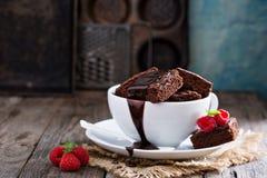 Nissen i staplade kaffekoppar med chokladsås Fotografering för Bildbyråer