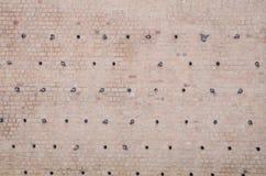Nisthöhlen in einer Backsteinmauer für Tauben Stockfotos