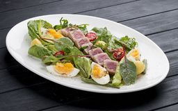 Nisuaz salad with tuna with anchovy sauce stock photos