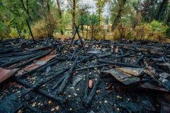 Niszczący pożarniczym drewnianym domem całkowicie palił ziemia zdjęcia stock