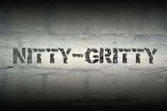 Nitty-gritty word gr. Nitty-gritty stencil print on the grunge white brick wall Stock Image