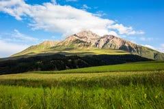 Niuxinberg, Qinghai, zijn er witte wolken op de bovenkant van de berg in de middag, de pieken onder de duidelijke hemel stock fotografie