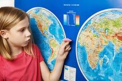 Nivå för flickainnehavpapper på världskarta arkivbilder