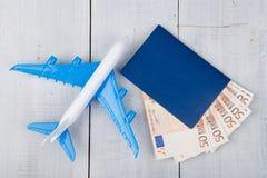 nivå, pass och pappers- pengar på den vita trätabellen arkivbild