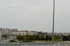 Nivån flyger över den olympiska byn Arkivbild