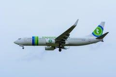 Nivån från Transavia PH-HSF Boeing 737-800 landar på den Schiphol flygplatsen Arkivfoto