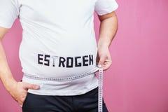 Niveau d'oestrogène, homme de poids excessif avec la bande de mesure image stock