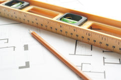 Niveau et stylo sur le plan d'architectes Photos stock