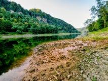 Nivel del agua baja, afluencia vacía del río Agua horrible fangosa del olor fotos de archivo