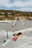 Nivel del laser en un trípode para formar un bloque de cemento Foto de archivo libre de regalías