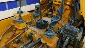 Niveladora amarilla con las conexiones caucho y mangueras metrajes