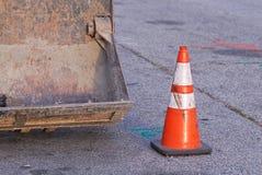Niveladora con el cono anaranjado rayado del tráfico en un poco de calle imagen de archivo