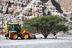 Niveladora estacionada al lado de árbol del acacia en Omán Fotografía de archivo libre de regalías