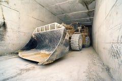 Niveladora grande en el túnel de mármol, Carrara, Italia imagen de archivo libre de regalías
