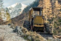 Niveladora que descansa en altas montañas después de trabajo imagenes de archivo