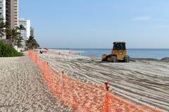 Niveladora que separa la nueva arena de la playa imágenes de archivo libres de regalías