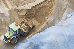 Niveladora que trabaja en la arena y campo de la roca en el uso del emplazamiento de la obra para el camino y construcción y urban Foto de archivo libre de regalías