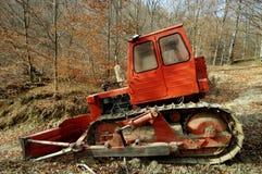 Niveladora roja en bosque Imagenes de archivo