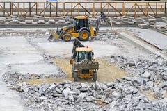 Niveladoras con agolpamiento de los martillos neumáticos y de los cubos y claro el sitio del hormigón bajo construcción en el Mam Fotografía de archivo libre de regalías