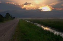 Nivelando, nuvens escuras, por do sol Fotografia de Stock