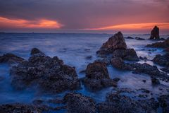 Nivelando o mar no cinza e no fundo alaranjado do céu imagens de stock royalty free