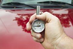 Niveles de Measuring PSI del mecánico en un neumático Fotos de archivo