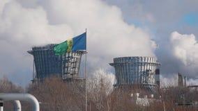 NIZHNEKAMSK, РОССИЯ - март 2018: трубы больших химиката и электростанции с излучениями, флага города в стоковое изображение