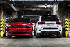 Nizhnevartovsk, Russia - August 24, 2016: Two Jeep Grand Cherokee SRT. Red and white, front and back view, parking stock photography