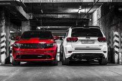Nizhnevartovsk, Russia - August 24, 2016: Two Jeep Grand Cherokee SRT. Red and white, front and back view, parking, black and white photo stock photos