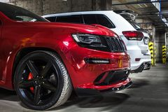 Nizhnevartovsk, Russia - August 24, 2016: Two Jeep Grand Cherokee SRT. Red and white, front side and back side view, black wheels stock image