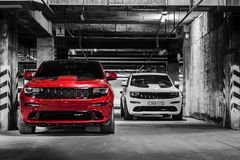 Nizhnevartovsk, Russia - August 24, 2016: Two Jeep Grand Cherokee SRT. Red and white, front view, parking, black and white photo stock photo