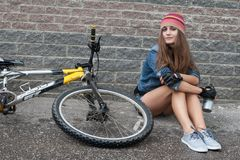 NIZHNIY NOVGOROD, ΡΩΣΊΑ - 7 ΙΟΥΛΊΟΥ 2012: Η φθορά κοριτσιών πλέκει με τη συνεδρίαση σακακιών τζιν και καπέλων σορτς στο ποδήλατό  Στοκ Εικόνες