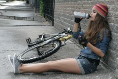 NIZHNIY NOVGOROD, RÚSSIA - 7 DE JULHO DE 2012: Malha vestindo da menina com revestimento da sarja de Nimes e short que senta-se e Fotografia de Stock