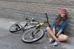 NIZHNIY NOVGOROD ROSJA, LIPIEC, - 21, 2012: Dziewczyna jest ubranym dzianinę z drelichową kurtką i skrótami siedzi z jej bicyklem Zdjęcie Royalty Free