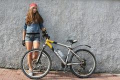 NIZHNIY NOVGOROD, RUSIA - 21 DE JULIO DE 2012: Muchacha atractiva que se coloca sobre la pared con su bicicleta Imagen de archivo