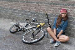 NIZHNIY NOVGOROD, RUSLAND - JULI 21, 2012: Meisje het dragen breit met denimjasje en borrels zittend met haar fiets bij muur Royalty-vrije Stock Foto