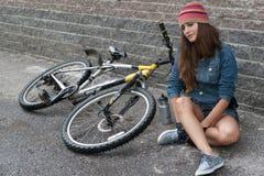 NIZHNIY NOVGOROD, RUSLAND - JULI 21, 2012: Meisje het dragen breit met denimjasje en van de borrelshoed zitting bij haar fiets Royalty-vrije Stock Foto's