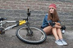 NIZHNIY NOVGOROD, RUSLAND - JULI 7, 2012: Meisje het dragen breit met denimjasje en van de borrelshoed zitting op haar fiets Stock Afbeeldingen